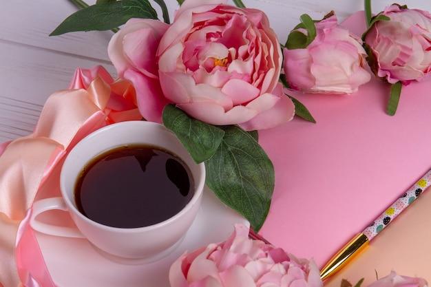 Filiżanka herbaty z kwiatami róży i piórem. notatnik z widokiem z góry z piórem.