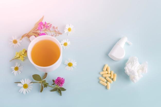 Filiżanka herbaty z kwiatami rumianku i kwitnącą sally i pigułkami, spray na katar i gardło. choroby sezonowe i leczenie przeziębień, grypy, upałów. ziołolecznictwo a medycyna konwencjonalna.