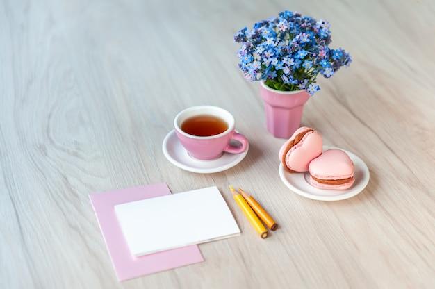 Filiżanka herbaty z makaronikami w kształcie serca, bukietem niezapominajek i kartka z tekstem gratulacyjnym na stole