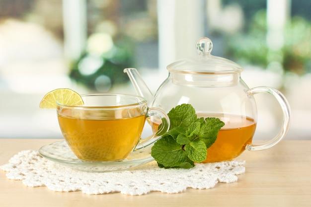 Filiżanka herbaty z miętą i limonką na stole w pokoju