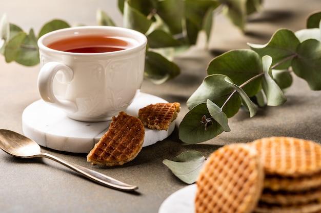 Filiżanka herbaty z mini stroopwafelem, ciasteczkami syrop waflowymi i gałązkami eukaliptusa na jasnej powierzchni