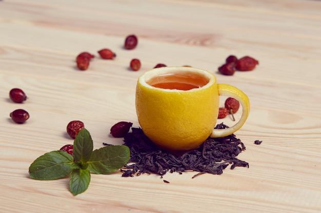 Filiżanka herbaty z modnymi różami na drewnianym stole. kubek wykonany z prawdziwej cytryny
