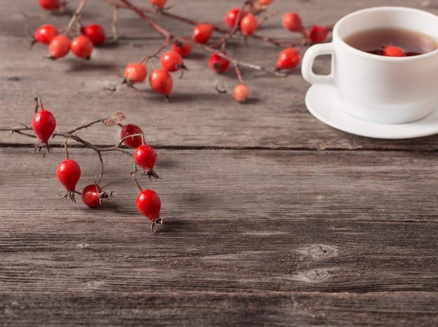 Filiżanka herbaty z modnymi różami na drewnianym stole
