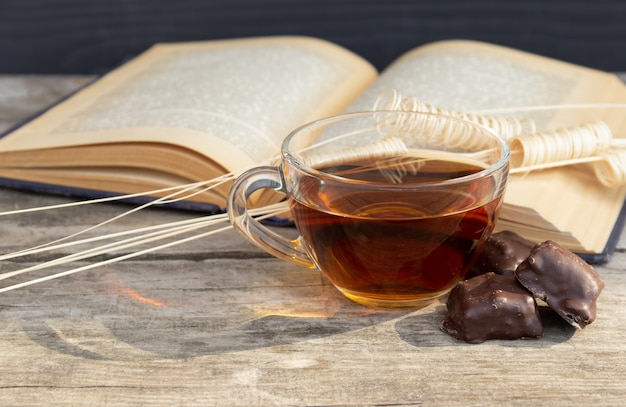 Filiżanka herbaty z otwartymi książkowymi i czekoladowymi cukierkami na drewnianym stole.
