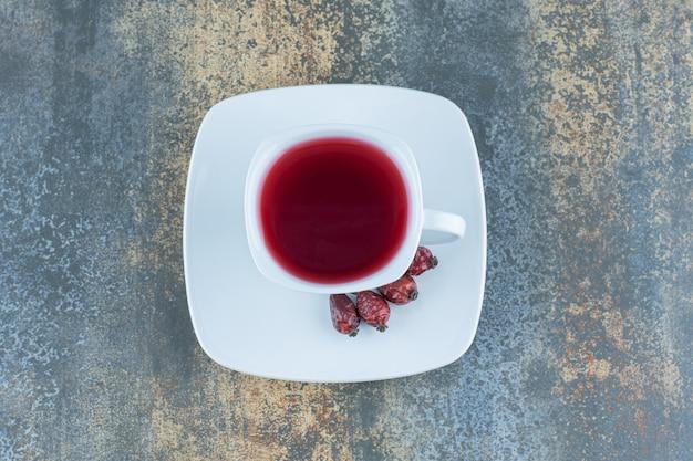 Filiżanka herbaty z owocami dzikiej róży na marmurze.