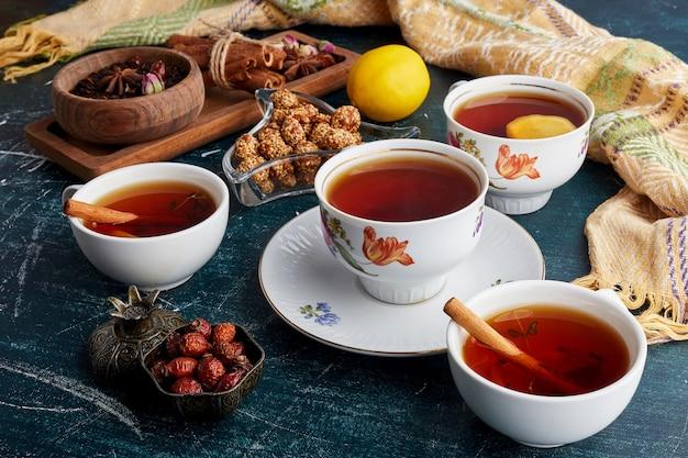Filiżanka herbaty z owocami, słodyczami i przyprawami.