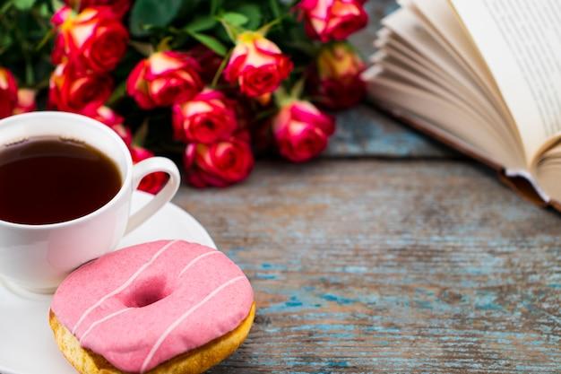 Filiżanka herbaty z pączkiem, świeżymi różami i książką na drewnianym.