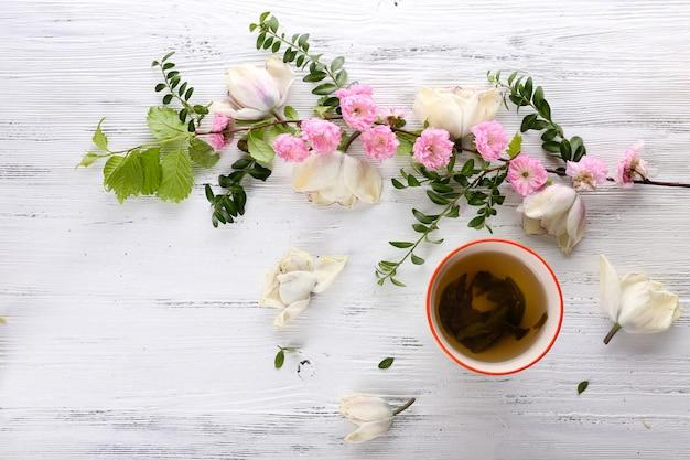 Filiżanka herbaty z pięknymi kwiatami na drewnianym