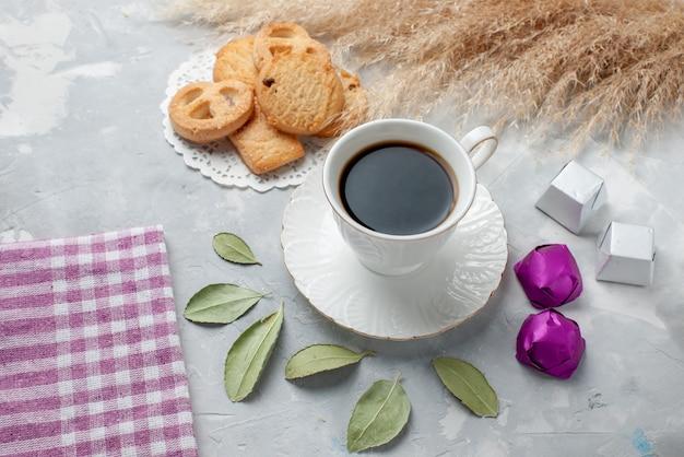 Filiżanka herbaty z pysznymi ciasteczkami cukierki czekoladowe na lekkiej podłodze ciastko herbatniki słodka herbata cukier