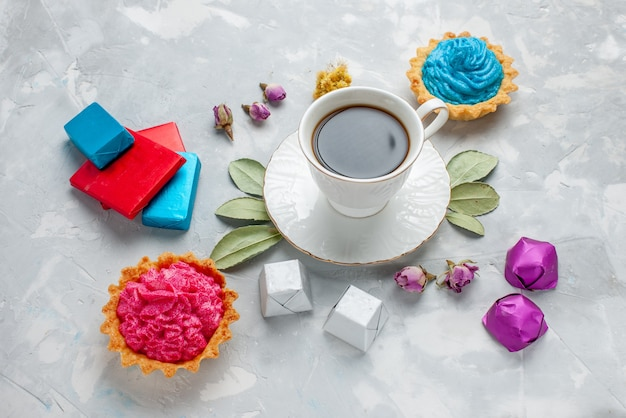 Filiżanka herbaty z różowymi kremowymi cukierkami czekoladowymi na lekkim biurku, biszkoptowe słodycze herbaciane