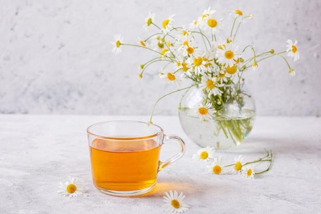 Filiżanka herbaty z rumiankiem i bukietem stokrotek w wazonie