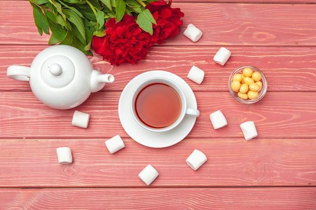 Filiżanka herbaty z słodyczy i kwiatów na drewnianym stole