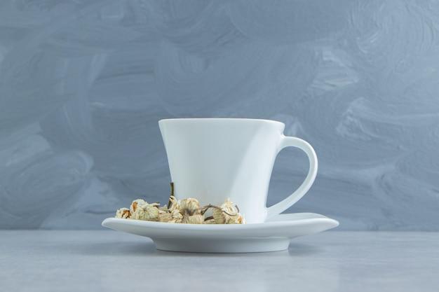 Filiżanka herbaty z suszonymi kwiatami rumianku.