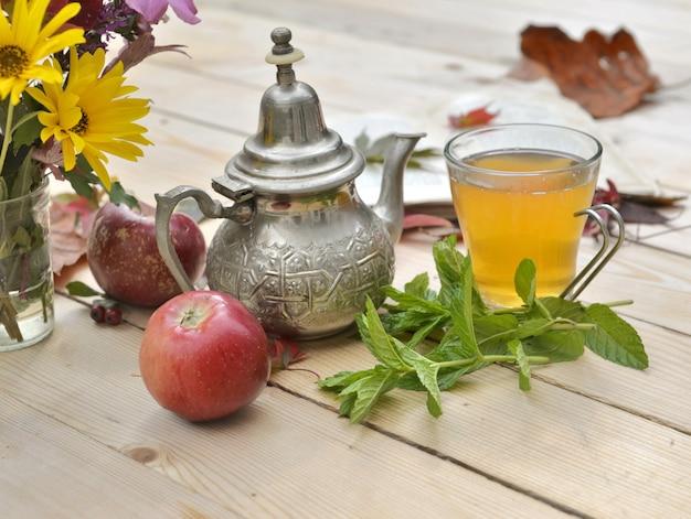 Filiżanka herbaty z świeżych liści mięty na drewnianym stole