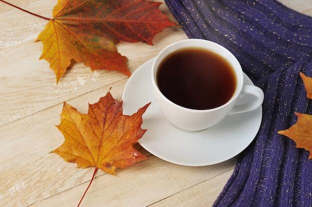 Filiżanka herbaty z szalikiem i jesiennymi liśćmi klonu - jesienna martwa natura