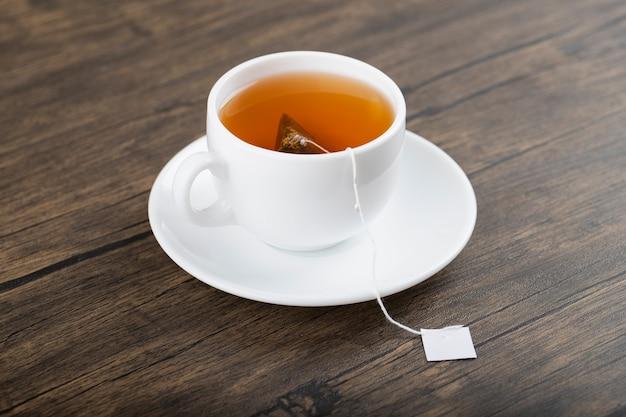 Filiżanka herbaty z torebką na drewnianym stole