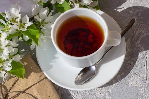 Filiżanka herbaty z wśród świeżego wiosennego kwiatu. śniadanie na świeżym powietrzu w słoneczny dzień. ładne pudełko ozdobne owinięte prostym brązowym papierem rzemieślniczym i ozdobione jutą.