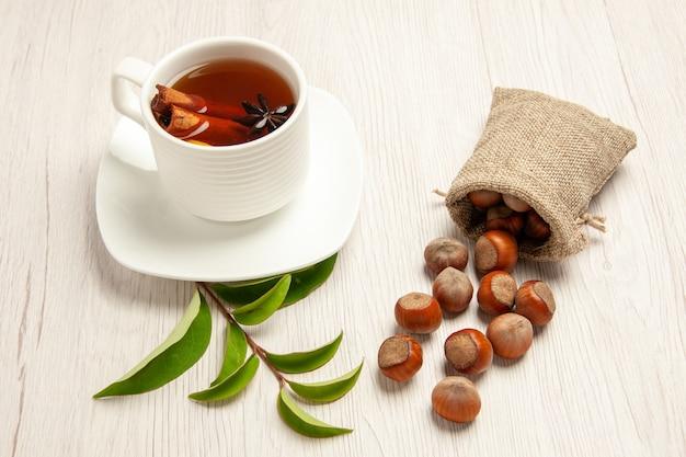 Filiżanka herbaty ze świeżymi orzechami laskowymi na białym tle