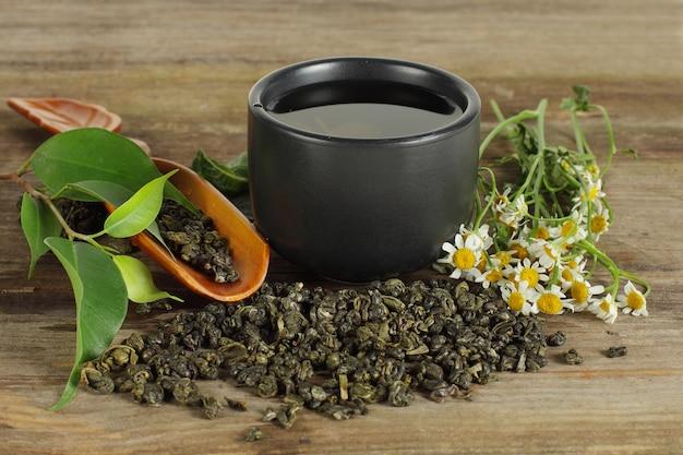 Filiżanka herbaty, zielony liść i rumianek