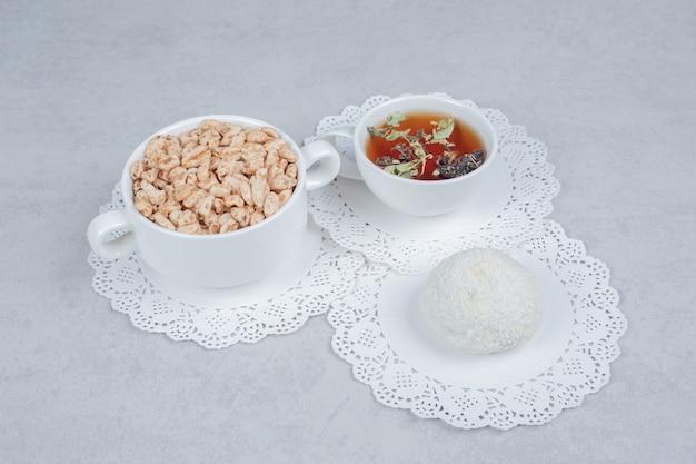 Filiżanka herbaty ziołowej, ciasteczka kokosowe i miskę słodyczy na białym stole. wysokiej jakości zdjęcie