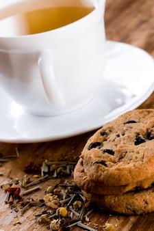 Filiżanka herbaty ziołowej i niektóre świeże ciasteczka zbliżenie na drewnianym stole