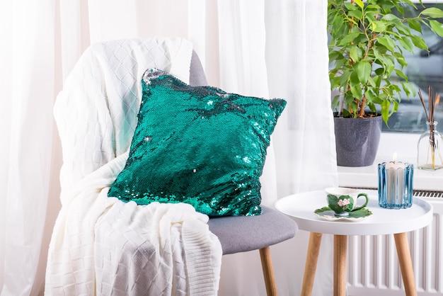 Filiżanka herbaty ziołowej na stole, wełniany koc z dzianiny, zielona cekinowa poduszka na krześle i świeca nad oknem. wnętrze sypialni