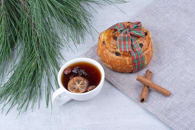 Filiżanka herbaty ziołowej z bułką z rodzynkami na obrusie. zdjęcie wysokiej jakości
