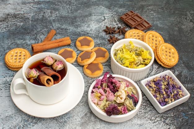 Filiżanka herbaty ziołowej z ciasteczkami i cynamonem i suszonymi kwiatami na szaro