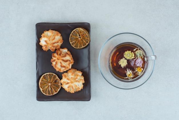 Filiżanka herbaty ziołowej z ciasteczkami i suszonymi pomarańczami na czarnym talerzu.