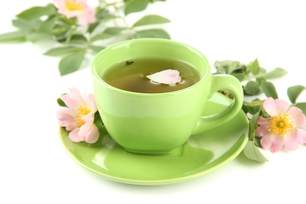 Filiżanka herbaty ziołowej z dzikimi kwiatami róży, na białym tle