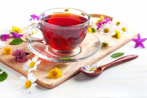 Filiżanka herbaty ziołowej z kwiatami i ziołami na tle drewnianych na tacy.