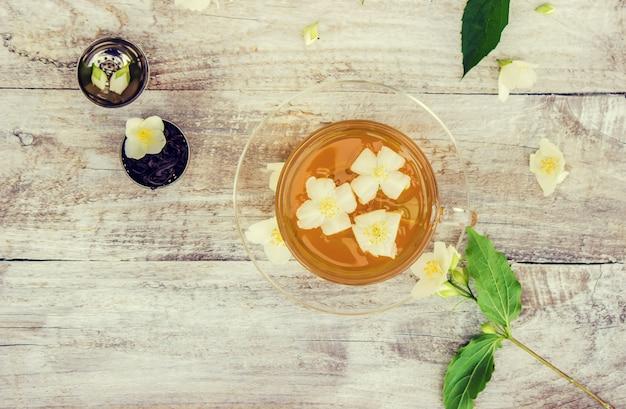 Filiżanka herbaty ziołowej z kwiatami jaśminu. selektywna ostrość.