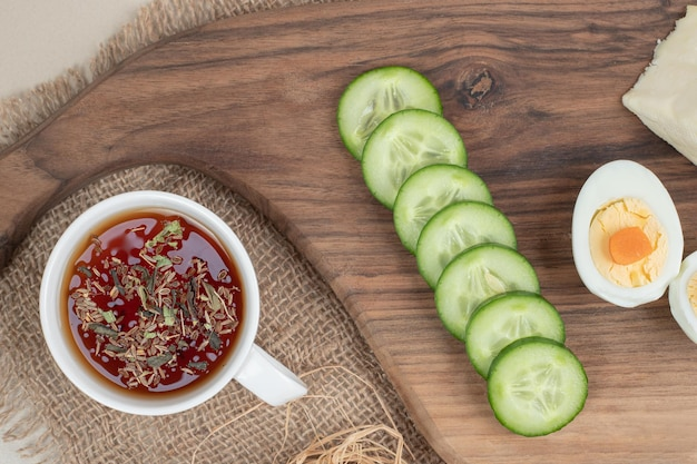 Filiżanka herbaty ziołowej z pokrojonym ogórkiem i gotowanym jajkiem.