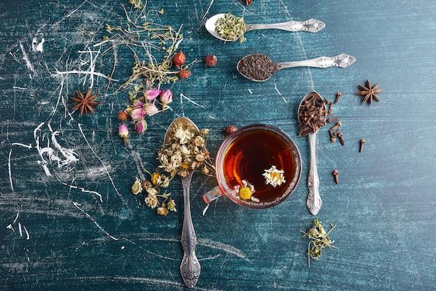 Filiżanka herbaty ziołowej z przyprawami dookoła.