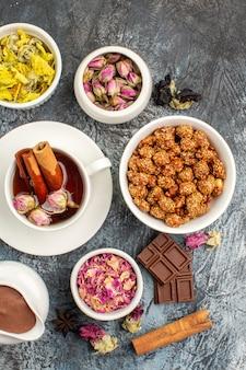Filiżanka herbaty ziołowej z różnymi suszonymi kwiatami i czekoladą oraz miska orzechów na szarym podłożu
