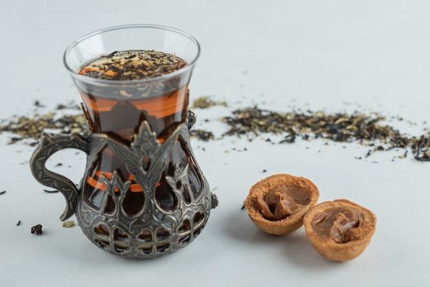 Filiżanka herbaty ziołowej ze słodkim ciasteczkiem w kształcie orzecha włoskiego.