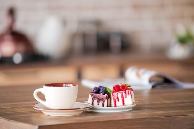 Filiżanka i ciastka na talerzu stoją na stole w kuchni