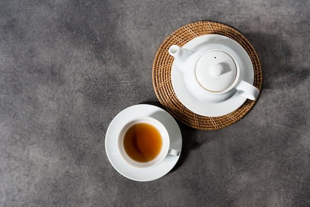 Filiżanka i czajnik z białej porcelany, angielska herbata na stole, popołudniowa herbata