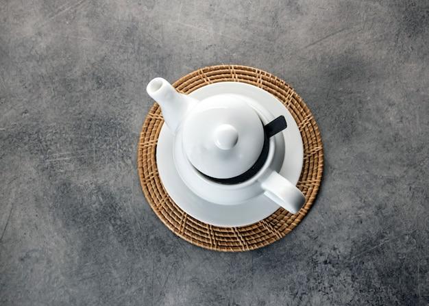 Filiżanka i czajnik z białej porcelany, ustawienie popołudniowego stołu