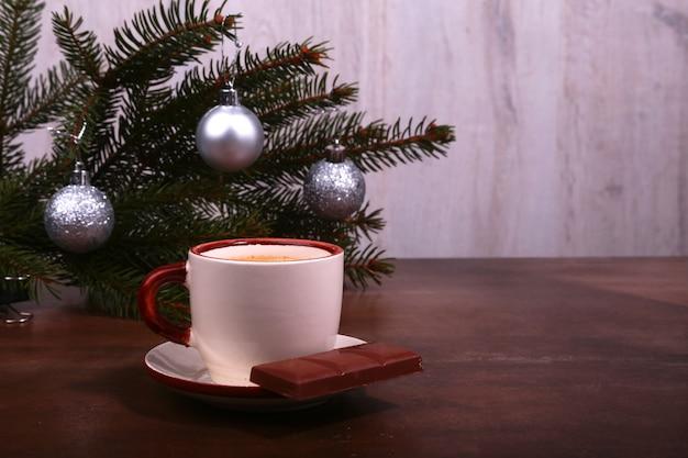 Filiżanka i czekolada na drewnianej stołowej teksturze. przerwa na kawę. czas świąt