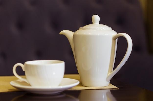 Filiżanka i dzbanek do herbaty na stole. śniadanie i herbata five o'clock. czas na herbatę.