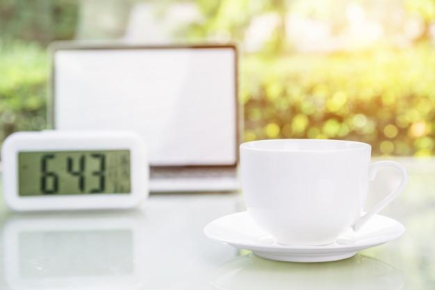Filiżanka i laptop przy biurem z cyfrowym zegarem