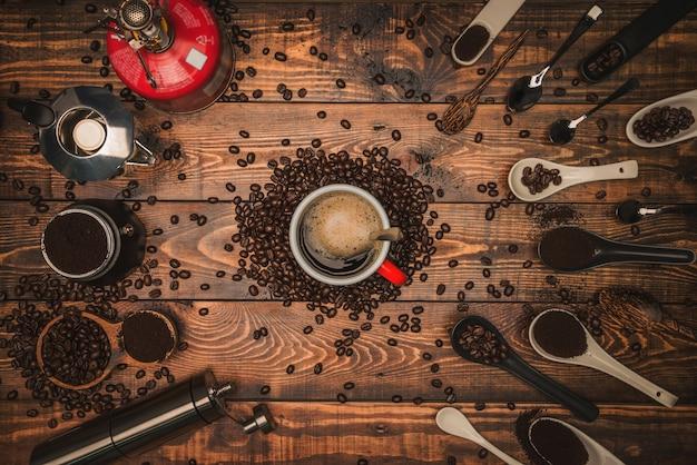 Filiżanka i młynek do kawy z innymi akcesoriami.