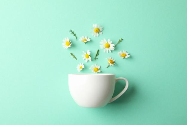Filiżanka i rumianki na mięcie. rumiankowa herbata