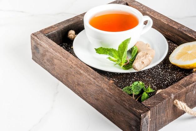 Filiżanka imbirowej herbaty z cytryną, świeżą miętą i miodem, w drewnianej tacy