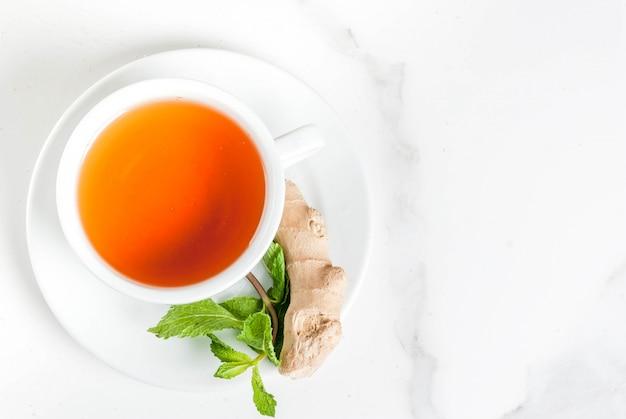 Filiżanka imbirowej herbaty z miętą lemonfresh i miodem na stole z białego marmuru