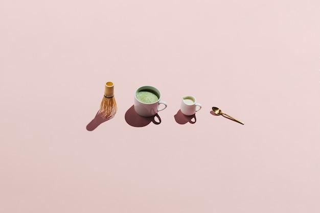 Filiżanka japońskiej herbaty matcha, bambusowa trzepaczka chasen, śmietanka i łyżeczka