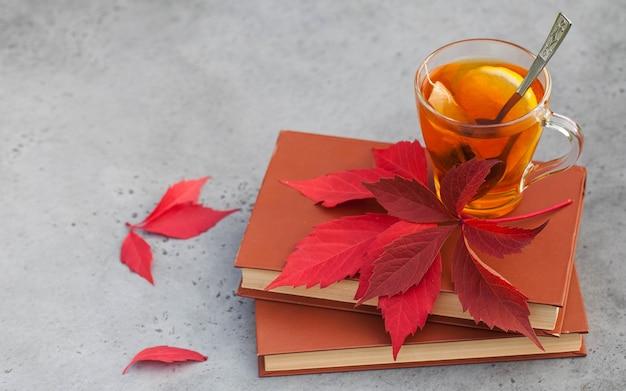 Filiżanka jesiennej herbaty na książkach gorący napój na jesienne zimne deszczowe dni. koncepcja hygge, jesienny nastrój.
