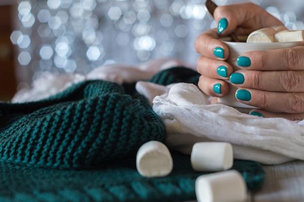 Filiżanka kakao z pianką marshmallow w kobiecych rękach z niebieskim manicure na błyszczącym tle