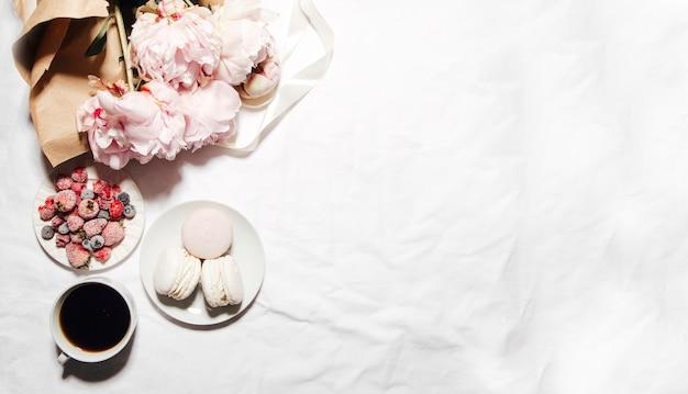 Filiżanka kawowych makaroników z jagodami i kwiatami piwonii na łóżku